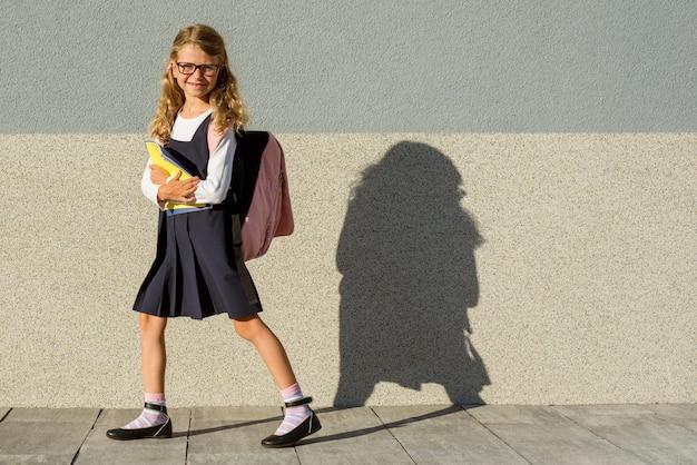 Uczennica szkoły podstawowej z zeszytami w ręku. Premium Zdjęcia