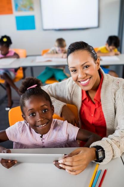 Uczennica Używa Pastylkę Przy Biurkiem Z Jej Nauczycielem Premium Zdjęcia