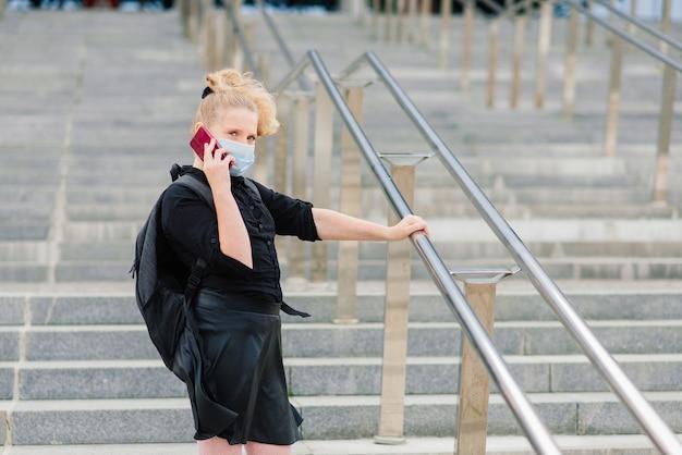 Uczennica W Ochronnej Masce Medycznej O Zachodzie Słońca. Współczesny Uczeń Z Plecakiem Podczas Kwarantanny Covid-19. Premium Zdjęcia