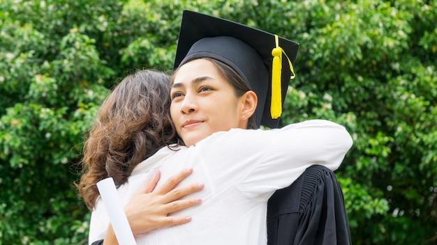 Uczennica w sukniach graduation i kapeluszu przytuliła rodzica podczas ceremonii gratulacyjnej. Premium Zdjęcia