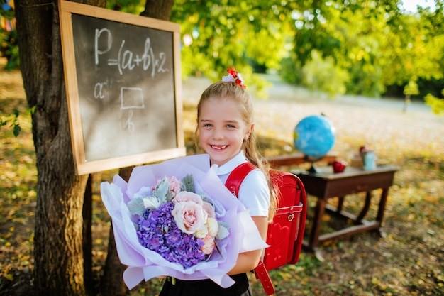 Uczennica Z Teczką I Bukietem Kwiatów Premium Zdjęcia