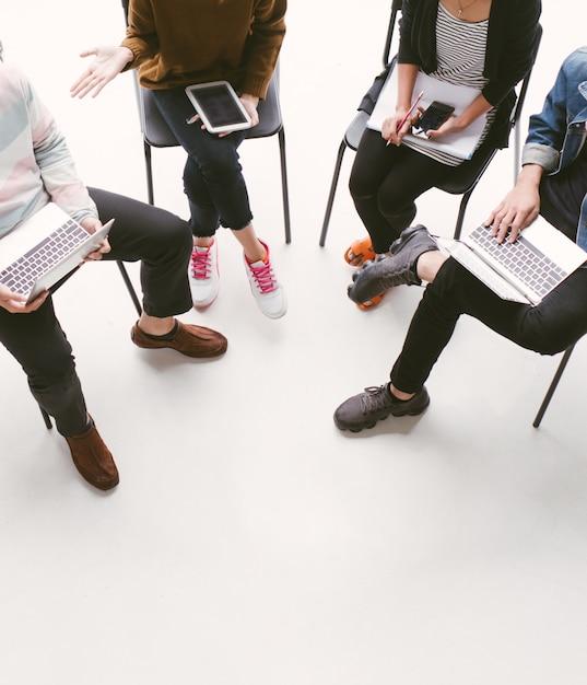 Uczniowie siedzą w kręgu przyjaciół, rozmawiając ze sobą na laptopie i tablecie Premium Zdjęcia
