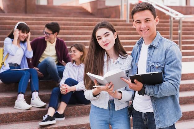 Uczniowie Stojąc Z Otwartymi Książkami I Patrząc Na Kamery Premium Zdjęcia