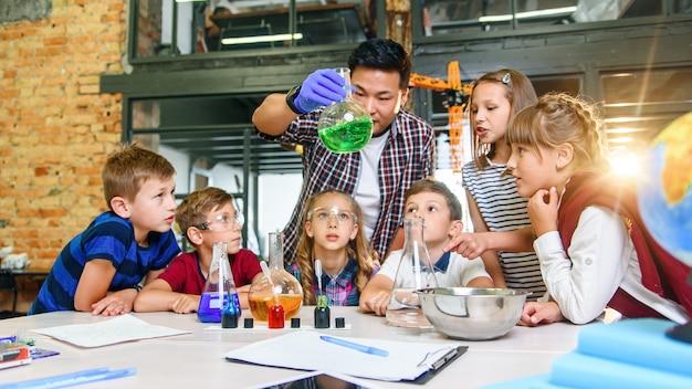 Uczniowie Szkoły Podstawowej Uważnie Przyglądają Się Swojemu Nauczycielowi, Który Pokazuje Ciekawe Eksperymenty Chemiczne Z Kolorowymi Cieczami W Szklanych Płaszczyznach. Premium Zdjęcia