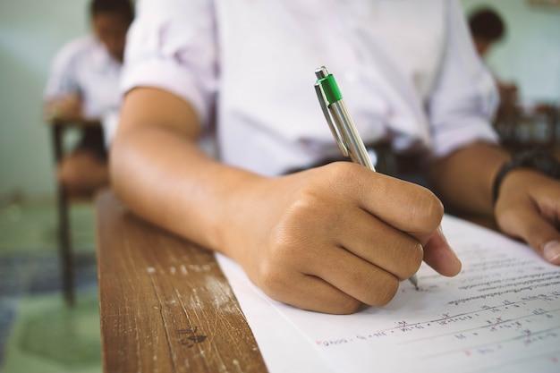 Uczniowie trzymają pióro w ręku robi egzaminy arkusze odpowiedzi ćwiczenia w klasie ze stresem. Premium Zdjęcia