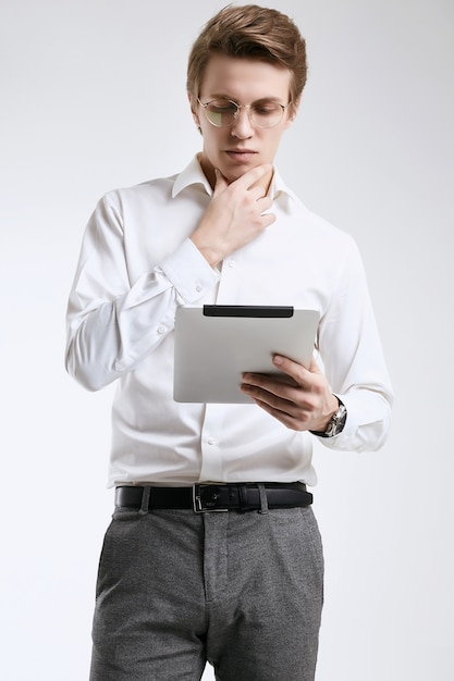 Ufny młody biznesmen w koszula pracuje na cyfrowej pastylce Premium Zdjęcia