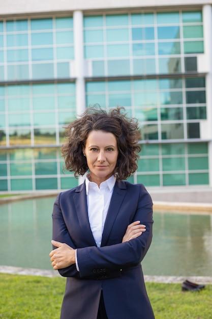 Ufny w średnim wieku bizneswoman pozuje blisko budynku biurowego Darmowe Zdjęcia