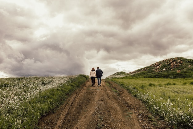 Ujęcie Mężczyzny I Kobiety Idących ścieżką W Dolinie Z Kwiatami Pod Mglistym Niebem Darmowe Zdjęcia