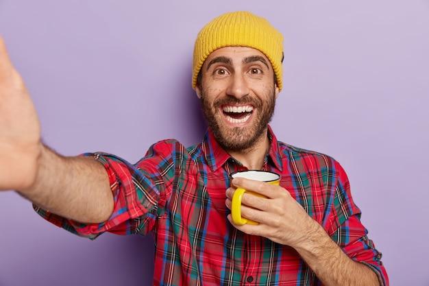 Ujęcie Szczęśliwego Mężczyzny Rasy Kaukaskiej Robi Selfie W Pomieszczeniu, Trzyma Kubek Z Kawą Lub Herbatą, Lubi Przerwy I Wolny Czas, Nosi Stylowy żółty Kapelusz I Koszulę W Kratę Na Fioletowej ścianie. Ludzie I Styl życia Darmowe Zdjęcia
