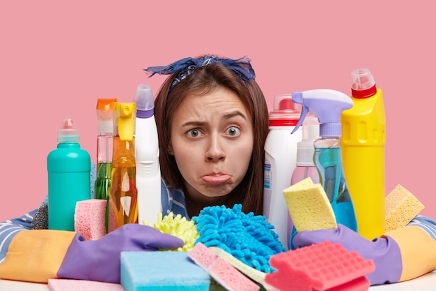 Ujęcie W Głowę Niezadowolonej Młodej Kobiety Zaciska Dolną Wargę Z Niezadowoleniem, Ma Dużo Pracy, Obejmuje Wiele Chemicznych Detergentów I Gąbek Darmowe Zdjęcia