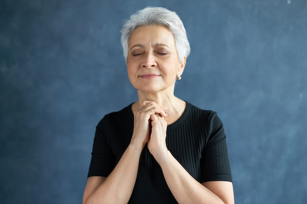 Ujęcie W Głowę Spokojnej Pięknej Dojrzałej Kobiety Z Krótkimi Siwymi Włosami, Odizolowanej, Z Pełnym Nadziei Wyrazem Twarzy, Z Zamkniętymi Oczami, Trzymającymi Ręce Złożone W Modlitwie, Z Nadzieją Na Najlepsze Darmowe Zdjęcia