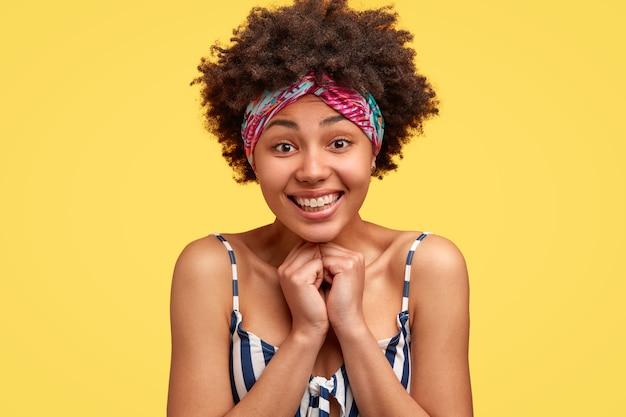 Ujęcie W Głowę Zadowolonej, Dotkniętej Młodej Afroameryki, Uśmiechającej Się Delikatnie, Czuje Się Zadowolona, Nosi Top W Paski I Nakrycie Głowy Darmowe Zdjęcia