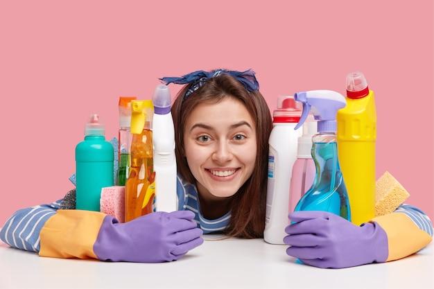 Ujęcie W Głowę Zadowolonej Uśmiechniętej Kobiety, Przyjazny Wygląd, Obejmuje Butelki Z Detergentem, Nosi Rękawiczki, Myje Naczynia, Czyści Kuchnię Darmowe Zdjęcia