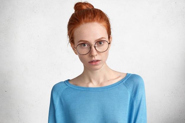 Ujęcie W Pomieszczeniu Pewnej, Poważnej Studentki Nosi Okulary, Ma Czerwone Włosy W Kok, Uważnie Słucha, Jakie Informacje Powinna Przygotować, Odizolowane Na Białym Tle Darmowe Zdjęcia