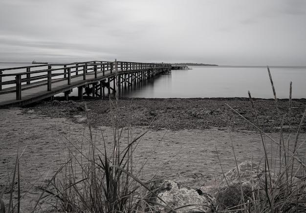 Ujęcie W Skali Szarości Molo Na Morzu Otoczonym Plażą Pod Zachmurzonym Niebem Darmowe Zdjęcia