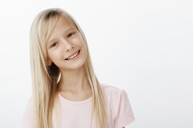 Ujęcie W Talii Beztroskiej Radosnej Kaukaskiej Dziewczyny O Blond Włosach, Przechylającej Głowę I Szeroko Uśmiechającej Się, Zadowolonej I Szczęśliwej Podczas Rozmowy Z Kolesiem Ze Szkoły, Który Lubi, Stojącej Nad Szarą ścianą Darmowe Zdjęcia