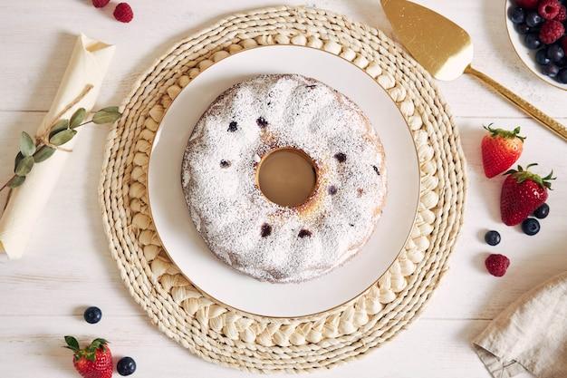 Ujęcie Z Ciasta Pierścieniowego Z Owocami I Proszkiem Na Białym Stole Z Białym Tłem Darmowe Zdjęcia