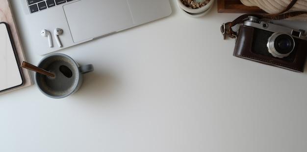 Ujęcie z góry wygodnego obszaru roboczego z laptopem, aparatem, filiżanką kawy i artykułami biurowymi na białym biurku Premium Zdjęcia