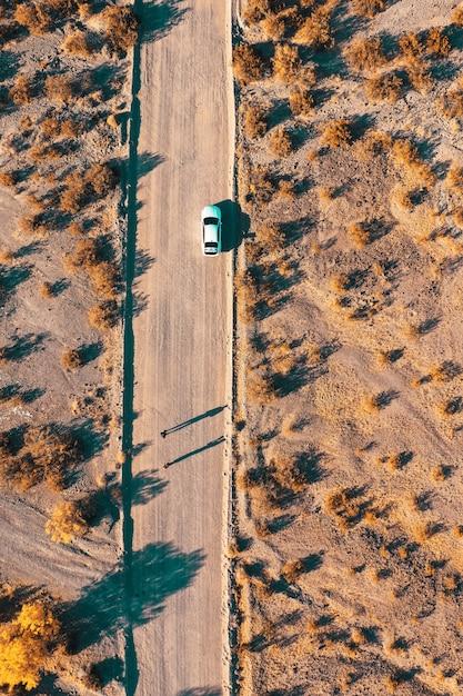 Ujęcie Z Lotu Ptaka Z Drona W Wąskiej Pustynnej Drodze Z Samochodem Na Poboczu Drogi Darmowe Zdjęcia
