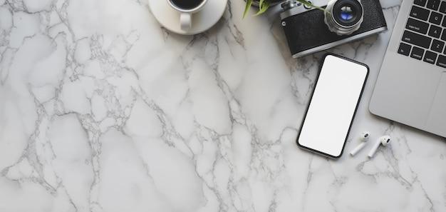 Ujęcie z miejsca pracy fotografa ze smartfonem i artykułami biurowymi Premium Zdjęcia
