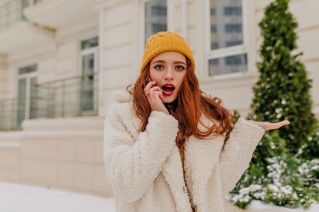 Ujmująca Pani O Ciemnych Falujących Włosach Rozmawia Przez Telefon W Zimny Dzień. Zimowy Portret Niesamowitej Rudej Dziewczyny. Darmowe Zdjęcia