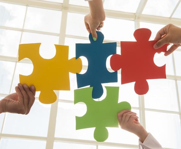 Układaj puzzle i reprezentuj koncepcję wsparcia i pomocy zespołu. Premium Zdjęcia