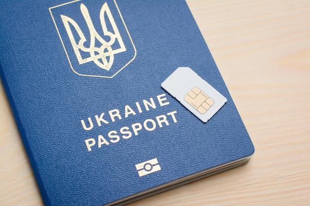 Ukraiński paszport biometryczny i karta sim na drewnie Premium Zdjęcia