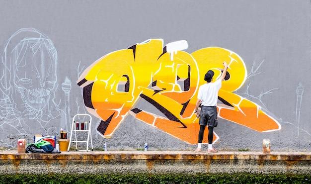 Uliczny Artysta Maluje Barwionych Graffiti Na Przestrzeni Publicznej ścianie Premium Zdjęcia