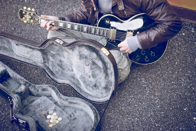 Uliczny Muzyk Bawić Się Gitarę Na Ziemi Premium Zdjęcia