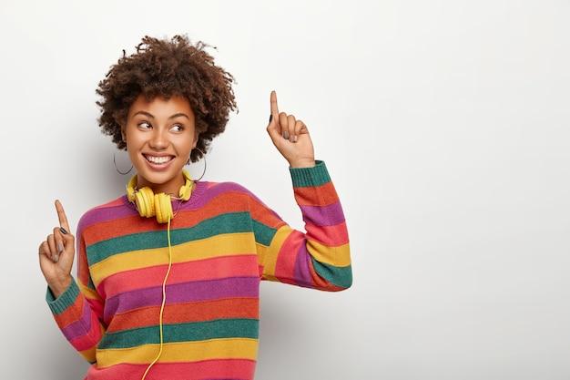 Ulubiona Piosenka Sprawia, że Tańczę. Urocza Nastolatka Podnosi Ręce, Wskazuje Palcami Wskazującymi W Górę, Słucha Muzyki Darmowe Zdjęcia