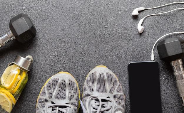 Uniwersalny Sprzęt Fitness Dla Kobiet I Mężczyzn Na Czarnym Tle Asfaltu Z Miejsca Kopiowania: Hantle, Telefon Ze Słuchawkami, Szare Trampki. Premium Zdjęcia