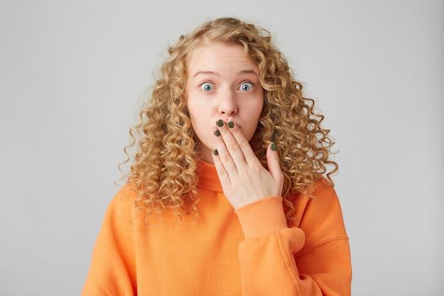Ups, Popełniłem Błąd! ładna I Atrakcyjna Blondynka Z Kręconymi Włosami Stoi Wpatrując Się W Kamerę, Zakrywa Usta Dłonią, Jakby Mówiąc Coś Wyjątkowego, Niestosownego, Zdradziła Czyjś Sekret. Darmowe Zdjęcia