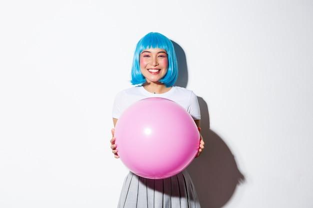 Urocza Azjatka świętuje Wakacje, Trzyma Balon I Nosi Niebieską Perukę Na Halloween, Stojąc. Darmowe Zdjęcia