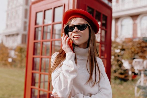 Urocza Dama Z Długimi Włosami W Czerwonej Czapce I Czarnych Okularach Stojąca W Pobliżu Czerwonej Budki Telefonicznej Darmowe Zdjęcia