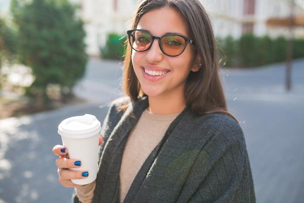 Urocza Dama Z Filiżanką Kawy Spacerująca Na Zewnątrz W Słoneczny Dzień Na Placu Miejskim Darmowe Zdjęcia