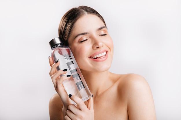 Urocza Dziewczyna Bez Makijażu Z Butelką Wody Na Odizolowanej ścianie. Uśmiechnięty Model Demonstruje Znaczenie Wody Dla życia. Darmowe Zdjęcia