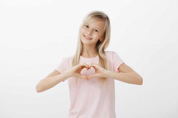 Urocza Dziewczyna Pokazuje Gest Serca I Uśmiecha Się Darmowe Zdjęcia