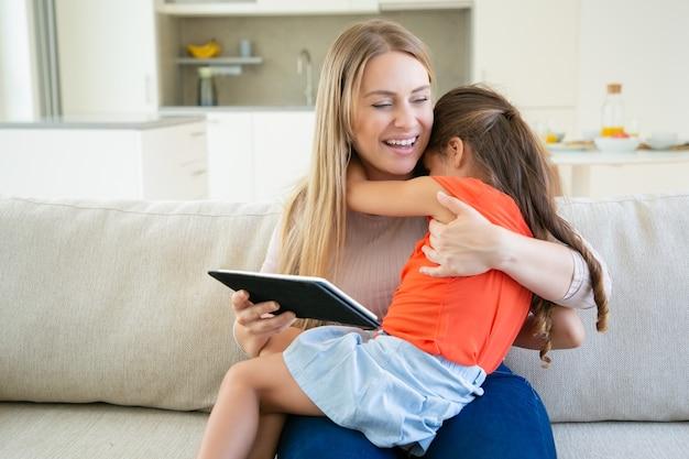 Urocza Dziewczyna Przytula Swoją Roześmianą Mamę, Gdy Używa Tabletu. Darmowe Zdjęcia