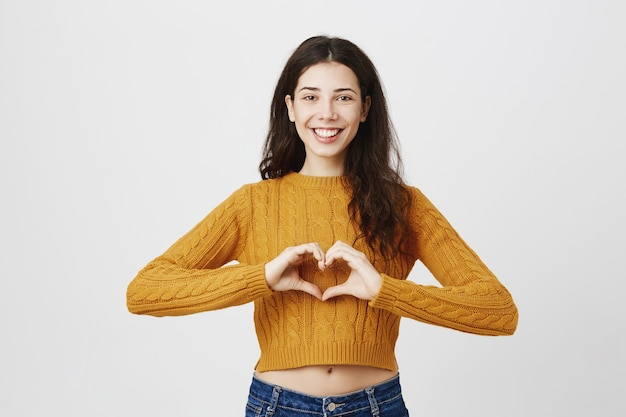 Urocza Dziewczyna Robi Gest Serca I Uśmiecha Się, Jak Produkt Darmowe Zdjęcia