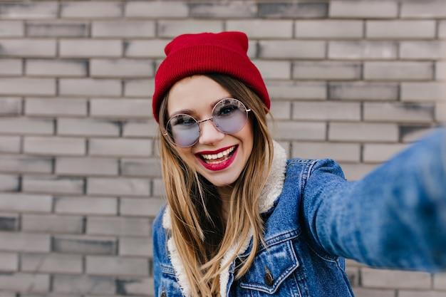 Urocza Dziewczyna W Niebieskich Okularach Robi Selfie Z Natchnionym Wyrazem Twarzy. Zdjęcie Pięknej Młodej Kobiety W Kapeluszu Robienia Zdjęć Na Ceglany Mur. Darmowe Zdjęcia
