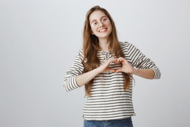 Urocza Dziewczyna W Okularach Pokazując Gest Serca I Uśmiechając Się Darmowe Zdjęcia
