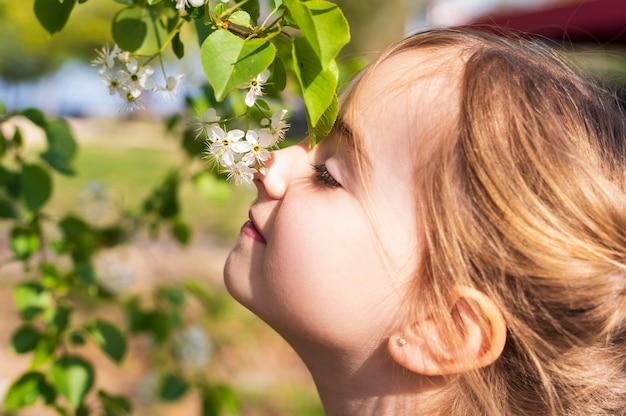 Urocza Dziewczyna Wącha Kwiatów Zamknięty Up Premium Zdjęcia