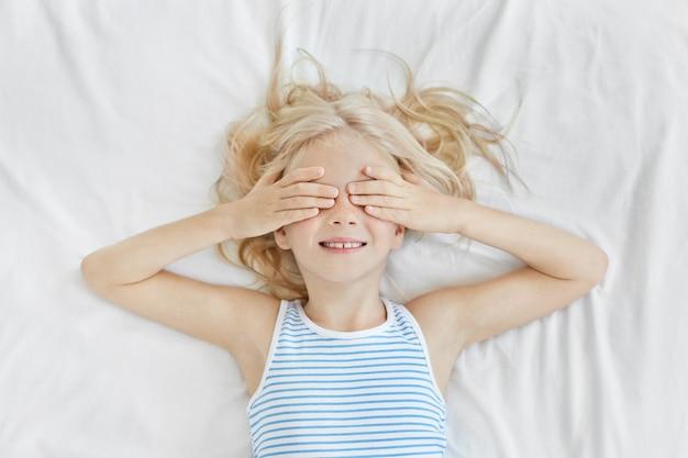 Urocza Dziewczynka Leżąca Na Białej Pościeli, Zakrywająca Oczy Rękami, Ubrana W Marynarski T-shirt, Uśmiechnięta Przed Snem. Blondyn Z Piegami Bawi Się W łóżku I Nie Chce Spać Darmowe Zdjęcia