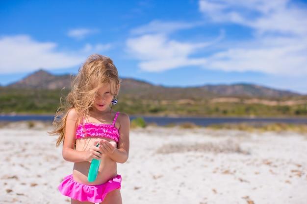 Urocza dziewczynka w strój kąpielowy z butelką balsam do opalania Premium Zdjęcia