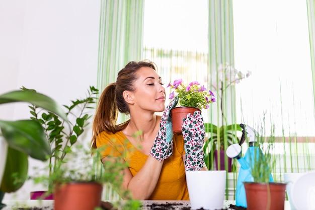 Urocza Gospodyni Z Kwiatkiem W Doniczce I Zestawem Ogrodniczym. Praca W Domu. Sadzenie Kwiatów I Wiosenne Porządki. Premium Zdjęcia