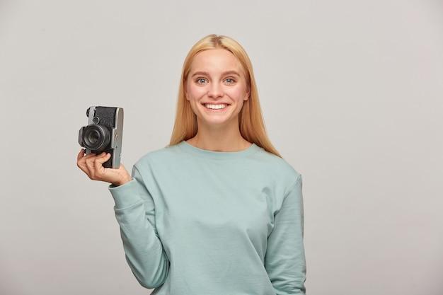 Urocza Kobieta Fotograf Wygląda Radośnie Uśmiechając Się, Trzymając W Jednej Ręce Aparat Fotograficzny Retro Vintage Darmowe Zdjęcia