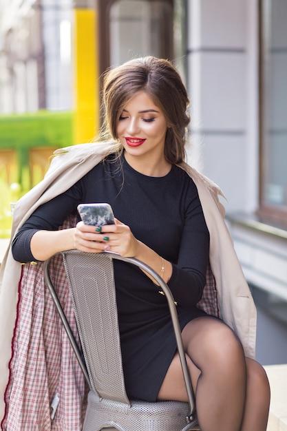 Urocza Kobieta Przewijająca Smartfon Podczas Odpoczynku W Mieście Darmowe Zdjęcia