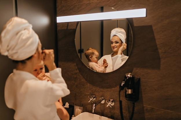 Urocza Kobieta W Szlafroku Nakłada Makijaż I Trzyma Dziecko. Mama I Córka Obserwują Poranne Zajęcia W łazience. Darmowe Zdjęcia