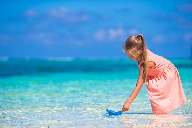 Urocza Mała Dziewczynka Bawić Się Z Origami łodzią W Turkusowym Morzu Premium Zdjęcia