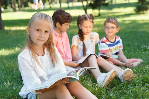 Urocza Mała Dziewczynka Czytając Książkę W Parku, Jej Przyjaciele Odpoczywają Na Trawie Na Tle Premium Zdjęcia